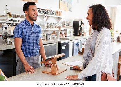 Female customer ordering at the counter in a coffee shop