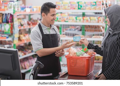 female customer paying cashless with credit card at the cashier in supermarket