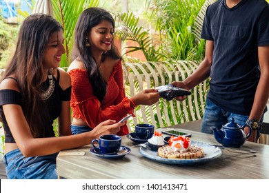 female Customer paying for coffee, pancakes with credit card sitting with laptop online shopping black friday sale.the waiter payment terminal while client doing contactless purchase in cafe