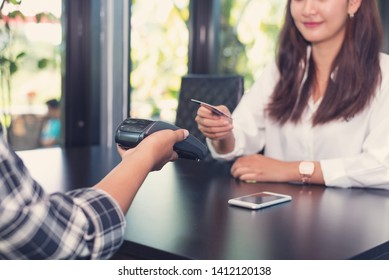Female customer paying with credit card with NFC technology. Man with a credit card reader machine at cafe with Asian girl holding credit card.