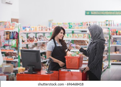 female customer paying her bills with credit card at the cashier in supermarket