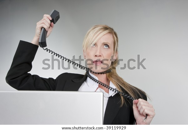 A female customer service agent shows her frustration with the telephone and computer.
