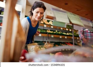 Female Customer With Shopping Basket Buying Fresh Apples In Organic Farm Shop