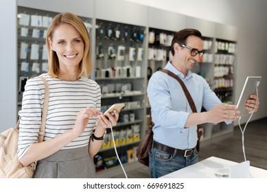 Female customer smiling into camera while man taking selfie