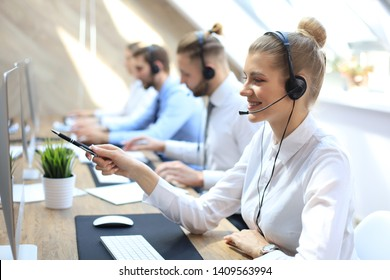Female customer support operator with headset and smiling.