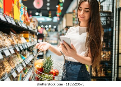 Female customer uses mobile phone in supermarket