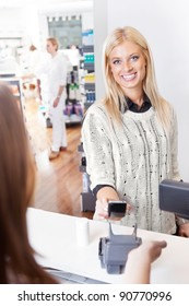 Female customer using cell phone to pay for goods