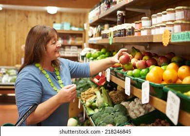Female Customer At Vegetable Counter Of Farm Shop