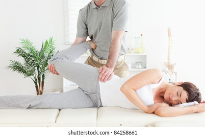 A female customer's leg is stretched by a chiropractor in his surgery