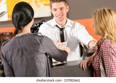 Female customers paying by cash czech crowns to cafe bartender