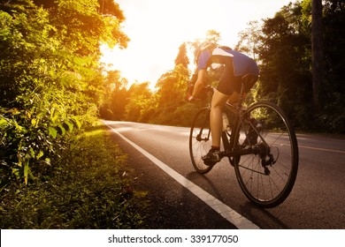 Female cyclist cycling am The path in the woods and mountains