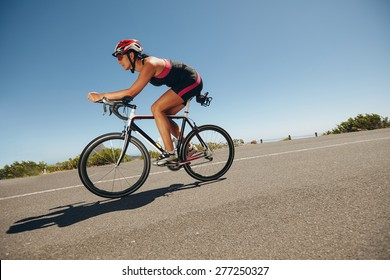 Female cyclist on a country road training for competition. Young woman riding bicycle down hill.