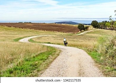 Female cyclist rides a bicycle on a hilly road to the Atlantic Ocean. Spain. Europe.