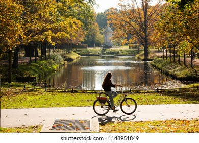 A female cyclist rides a bicycle in the Tiergarten park in Berlin