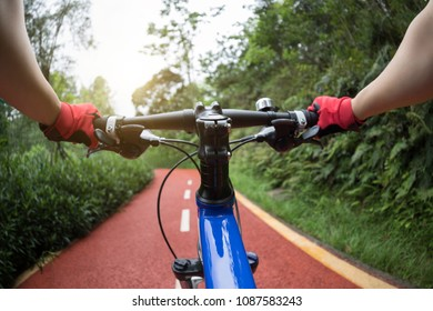 Female cyclist riding mountain bike on trail in forest