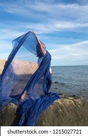 Female dancer in blue leotard and tights, waving huge blue fabric into the wind on the rocky beach at Hammonasset State Park in Madison, Connecticut.