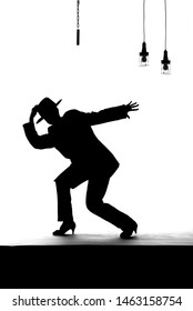 A female dancer dances on an old worn out stage. Dressed in men's clothing, she is seen dancing as a silhouette.