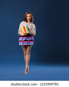 female dancer in miniskirt on tiptoe with pile of books on dark blue studio background