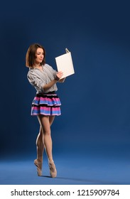 female dancer in miniskirt on tiptoe reading book on dark blue studio background