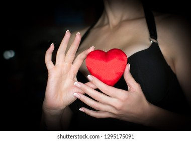Female decolletage, black dress. Woman holds a red silk heart in her hands, low key. Valentines Day, love or donor concept.