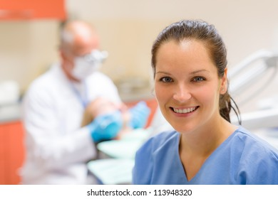 Female dental assistant smiling at stomatology office dentist with patient