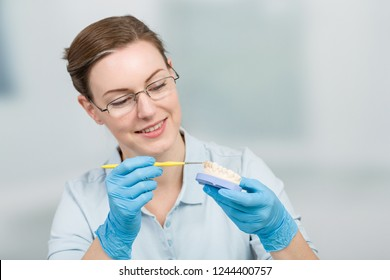 female dental technician works on tooth crown in dental laboratory