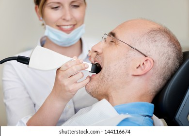 Female dentist with dental camera examining patient's teeth at clinic