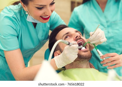 Female dentist examining and working on young male patient. Dentist's office.