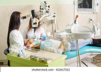 Female dentist and her assistant treating caries using microscope, wearing masks and gloves. Young blonde woman patient lying on dentist chair. Medical equipment. Dental clinic