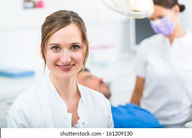 Female Dentist in her surgery looking at the viewer, in the background her assistant is giving a male patient a treatment