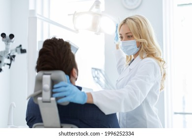 Female dentist in medical face mask turning on lamp, greeting male patient in dental chair, copy space. Young blonde woman stomatologist beginning treatment, turning on light