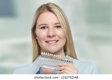 female dentist or patient with dental shade guide