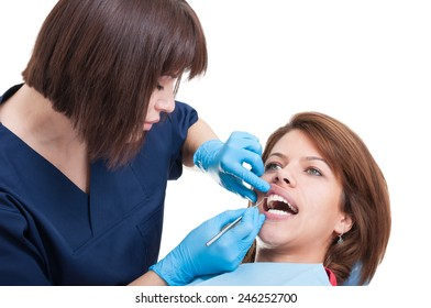 Female dentist performing the periodic oral exam