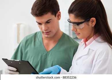 Female dentist showing something to her colleague on clipboard