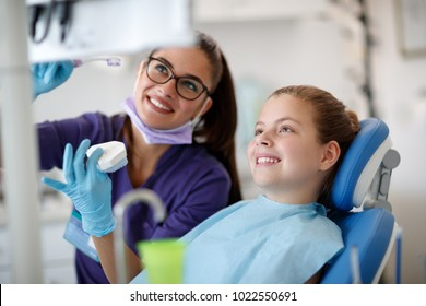 Female dentist talk about cleaning jaw with little patient