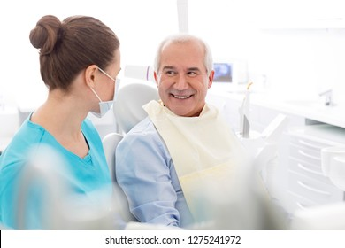 Female dentist talking to smiling senior patient at dental clinic