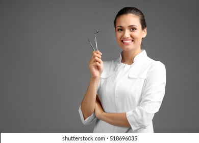 Female dentist with tools on grey background