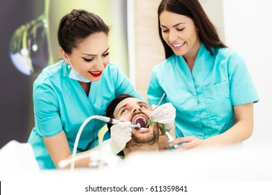 Female dentist treating male patient in dentist's chair, using dental drill.