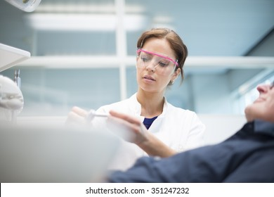A female dentist wearing protection goggles checking equipment while attending a patient