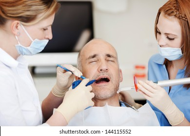 Female dentists using dental tools while examining patients mouth in clinic