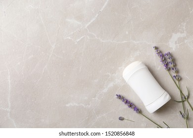 Female deodorant and lavender flowers on marble background, flat lay. Space for text