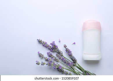 Female deodorant and lavender flowers on white background, top view