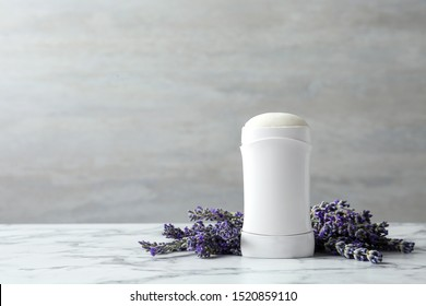 Female deodorant and lavender flowers on white marble table. Space for text