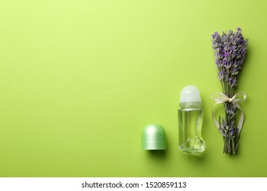 Female deodorant and lavender flowers on green background, flat lay. Space for text