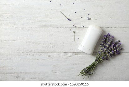 Female deodorant and lavender flowers on white wooden background, flat lay. Space for text