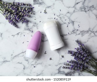 Female deodorant and lavender flowers on white marble background, flat lay