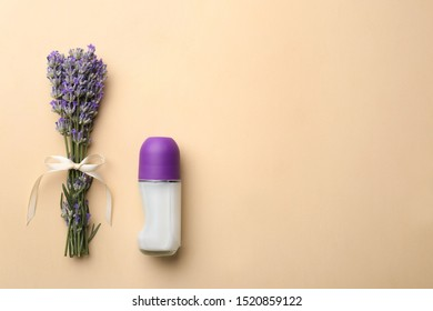 Female deodorant and lavender flowers on beige background, flat lay. Space for text