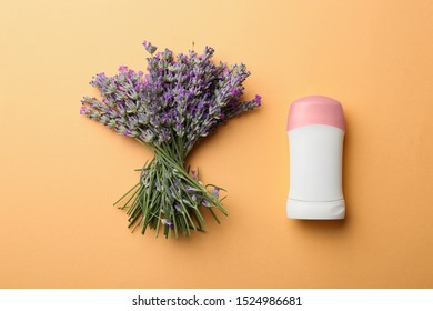 Female deodorant and lavender flowers on apricot background, flat lay