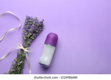 Female deodorant and lavender flowers on lilac background, flat lay. Space for text