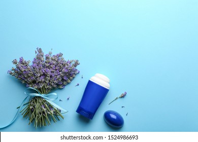 Female deodorant and lavender flowers on light blue background, flat lay